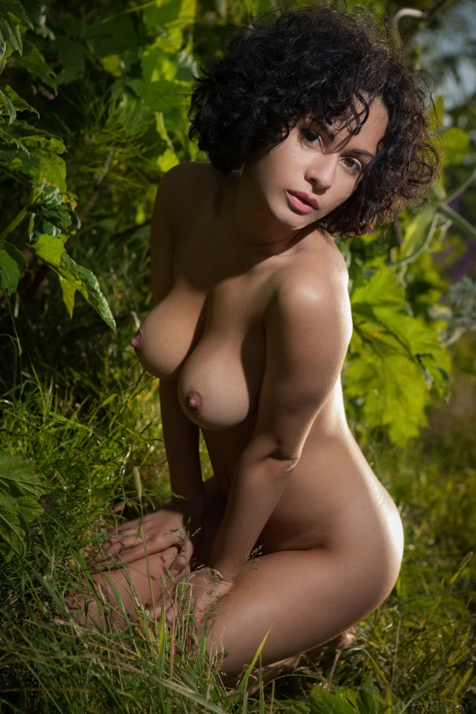 Curly-haired brunette in a see-through top undressing among the trees