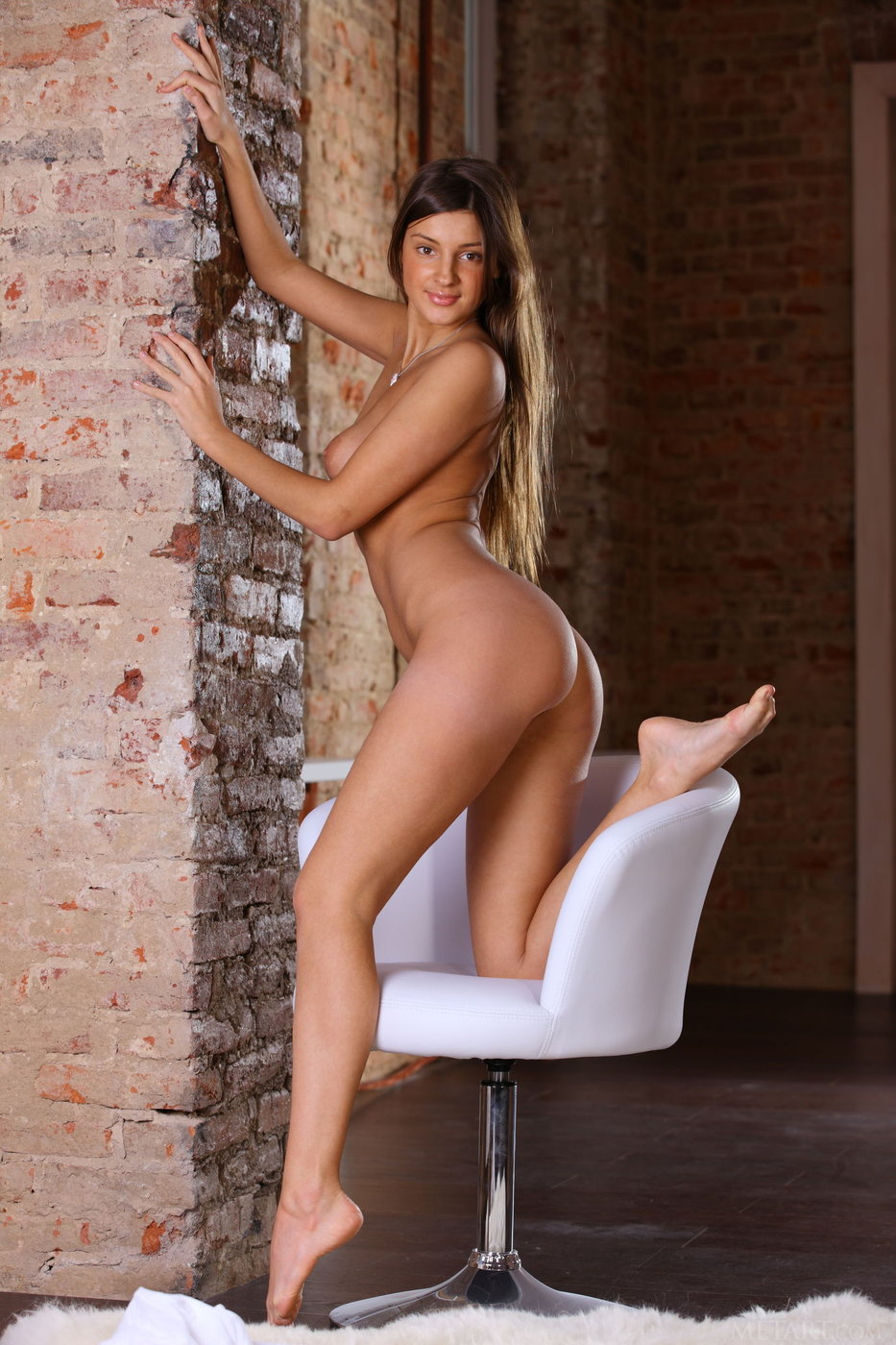White get-up tanned brunette showing those slender legs on a chair