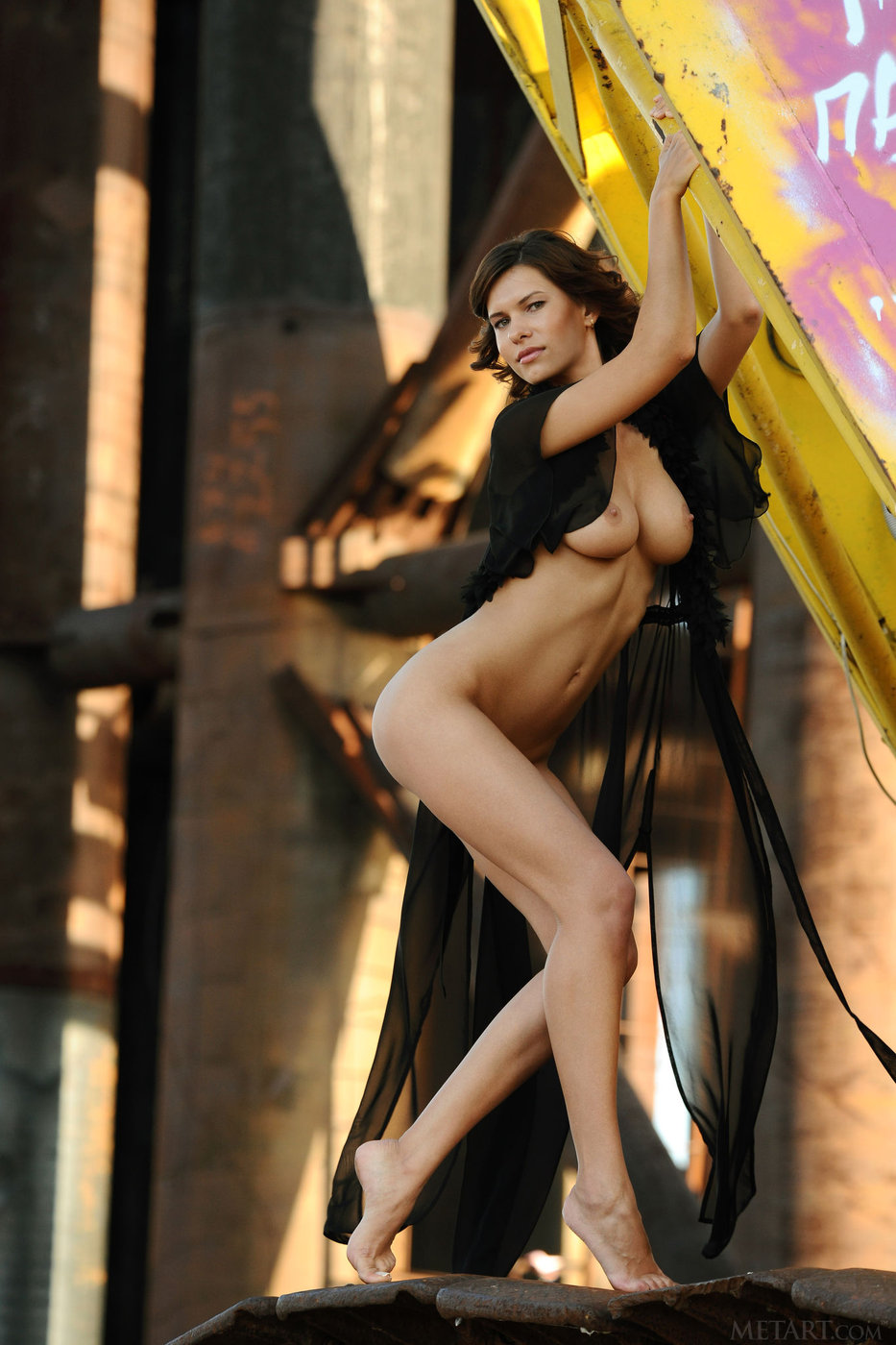 Short-haired brunette posing naked next to some heavy machinery