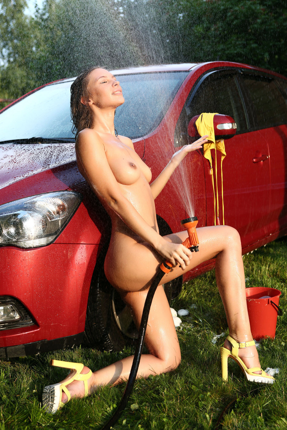 Wavy-haired brunette in bikini and her messy, wet, naked car wash