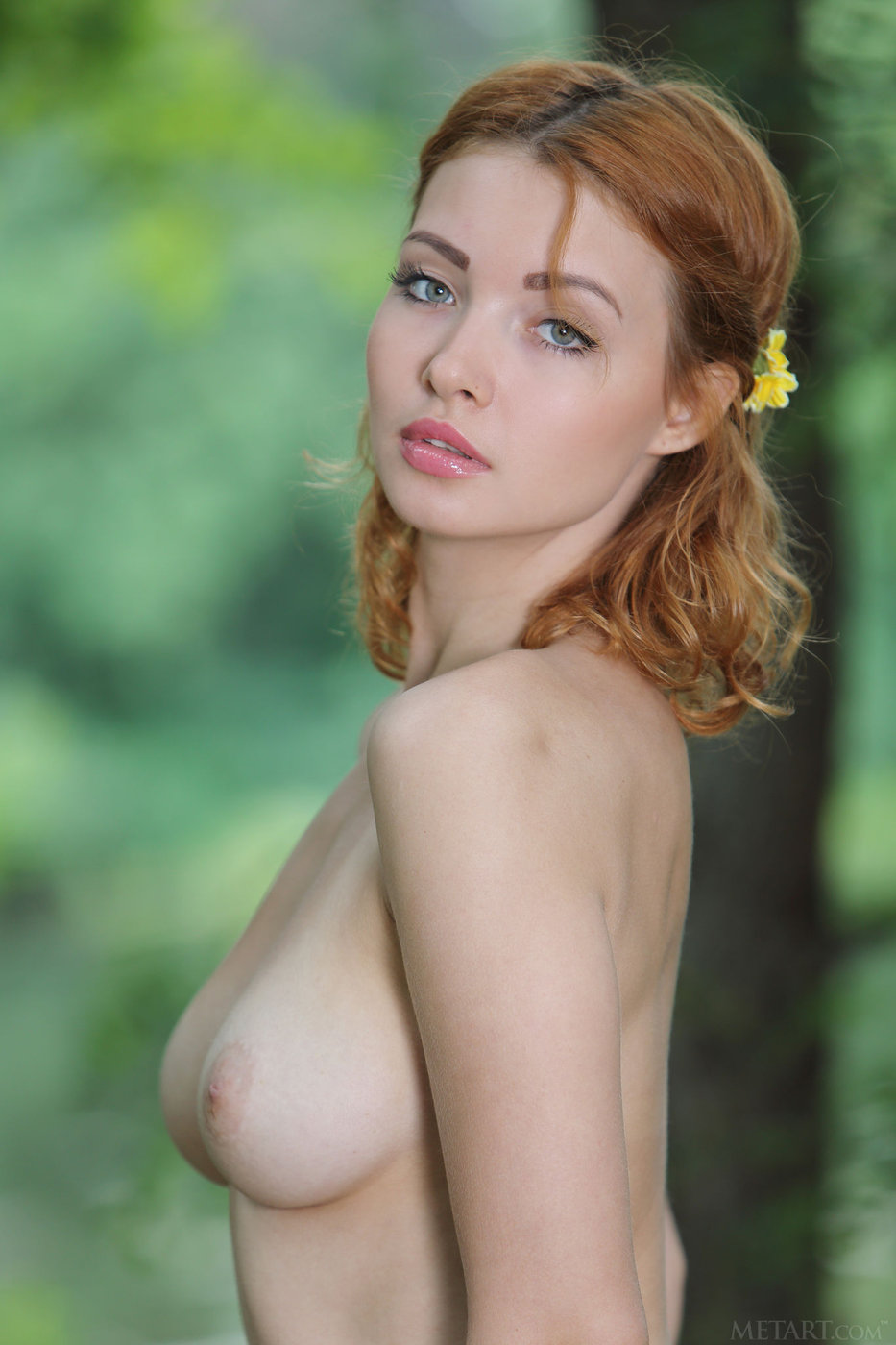 redhead with blue eyes shows her beautiful boobs in the forest