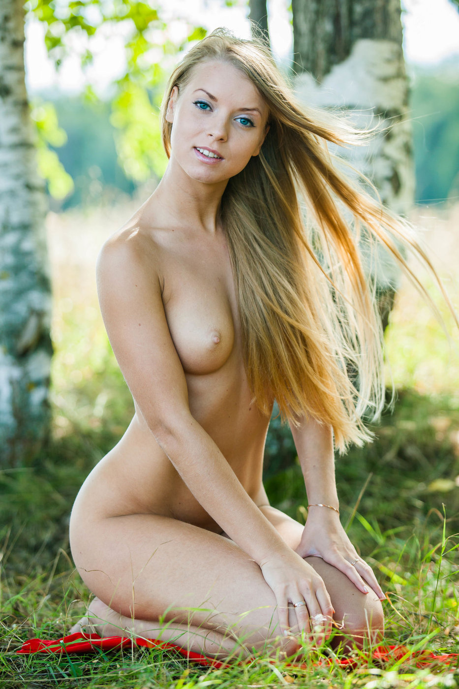 Blue-eyed blonde in red shows that amazing body of hers in the forest