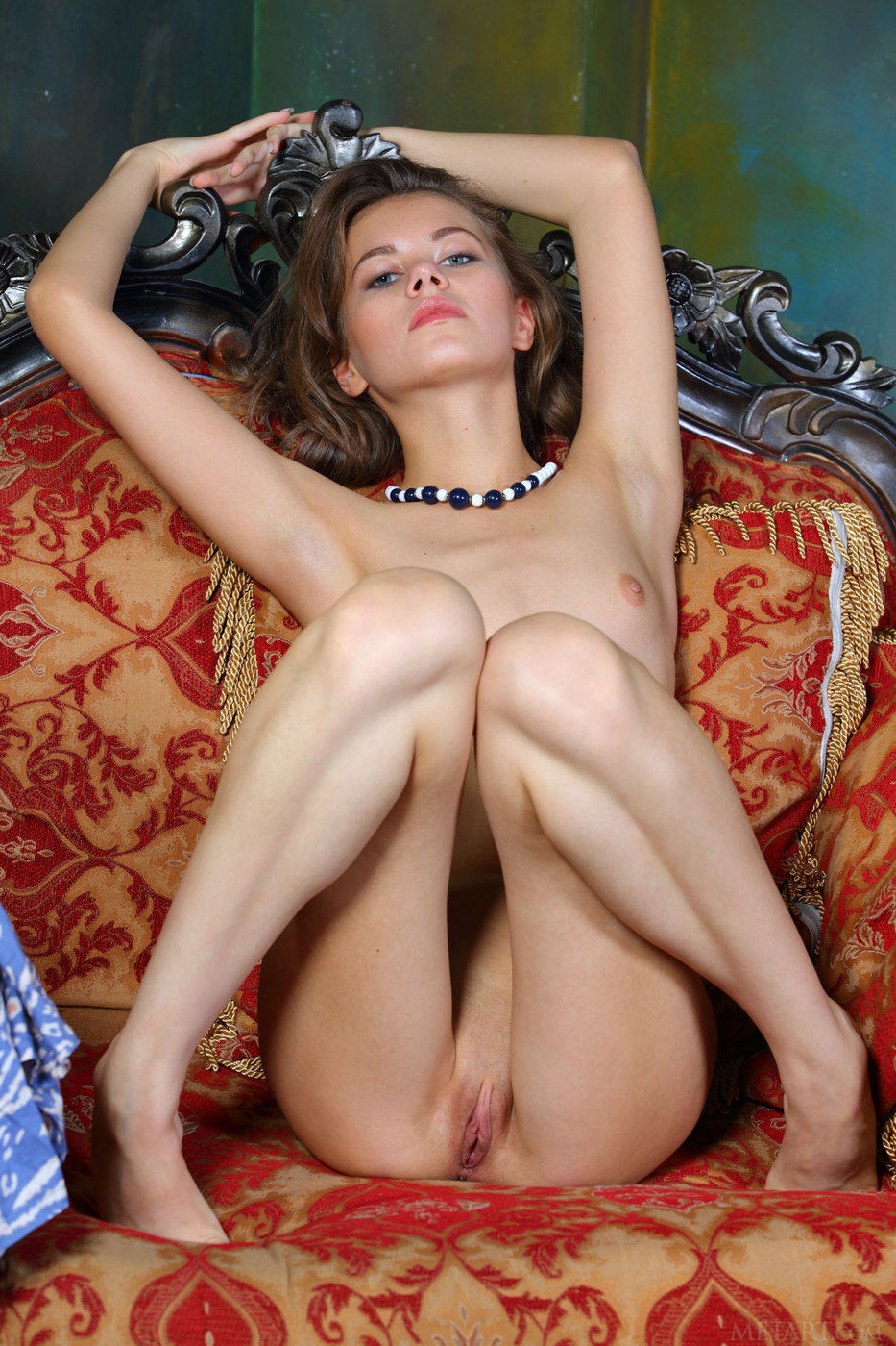 Flat-chested brunette with blue eyes posing naked on the sofa