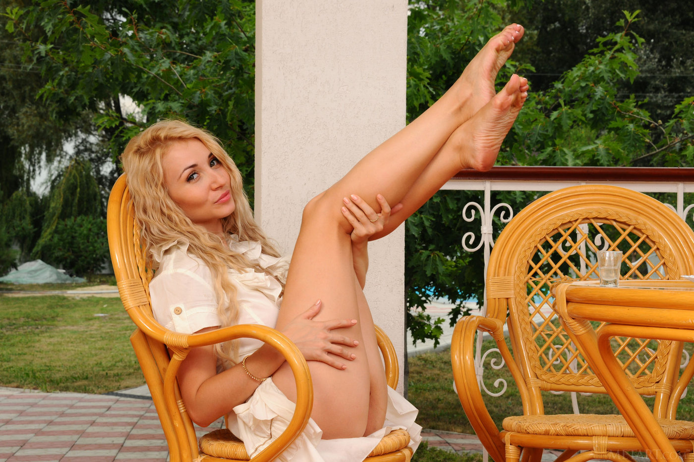 curly-haired and busty older blonde posing half-naked on a wicker