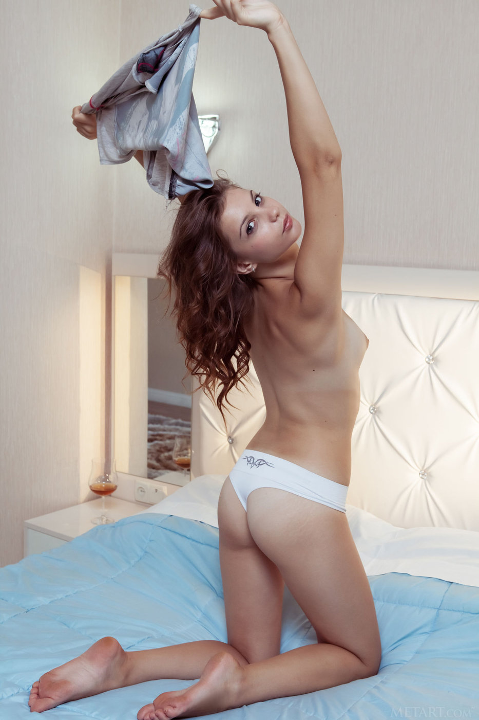 Teen takes off her white panties to pose stretched out on a bed