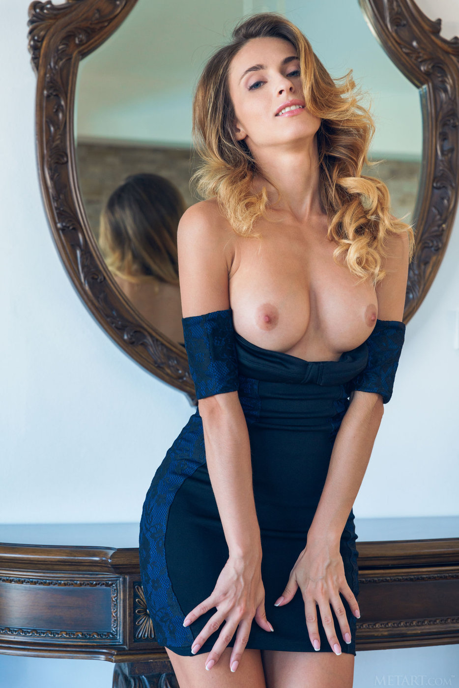 Busty blonde takes off her skintight navy blue dress and poses naked