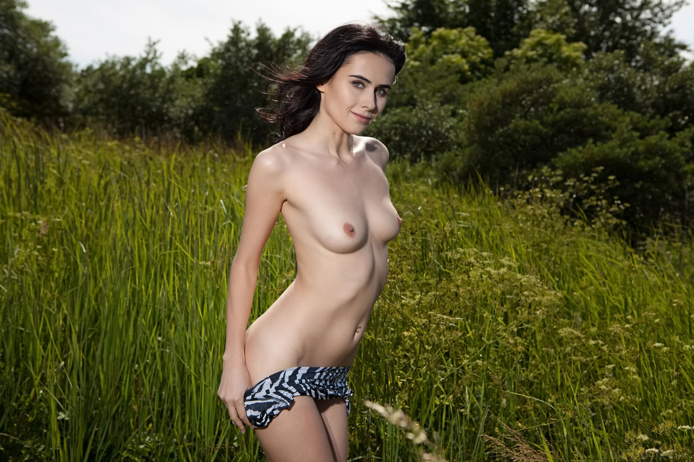 Leggy brunette with perky tits showing off her great body in a field