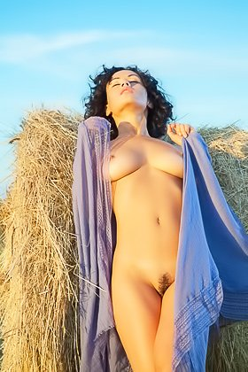 Curly-haired brunette with a blue blankie poses next to a haystack Videos