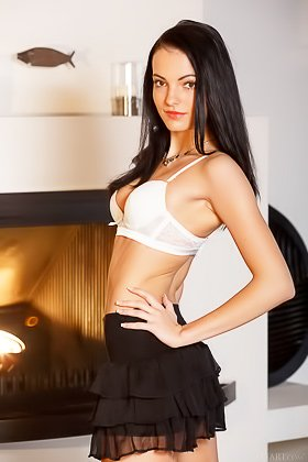 Tanned brunette in a black skirt shows off her pussy by the fireplace Videos