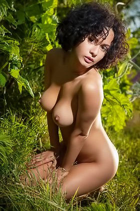 Curly-haired brunette in a see-through top undressing among the trees Videos
