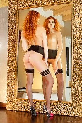 Curly-haired redhead in black stockings posing next to a mirror Videos