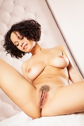 Curly-haired brunette in a white dress demonstrating her subtly hairy pussy Videos