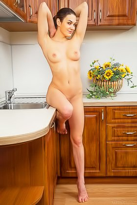 Dark-haired and impressive-looking brunette shows off on a kitchen counter Videos