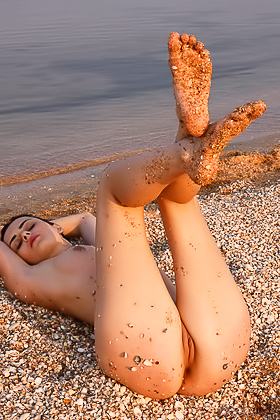 Busty brunette with a beautiful face posing naked on a rocky beach Videos