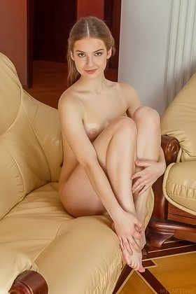 Blond-haired naked beauty lazily stretching in a huge armchair Videos
