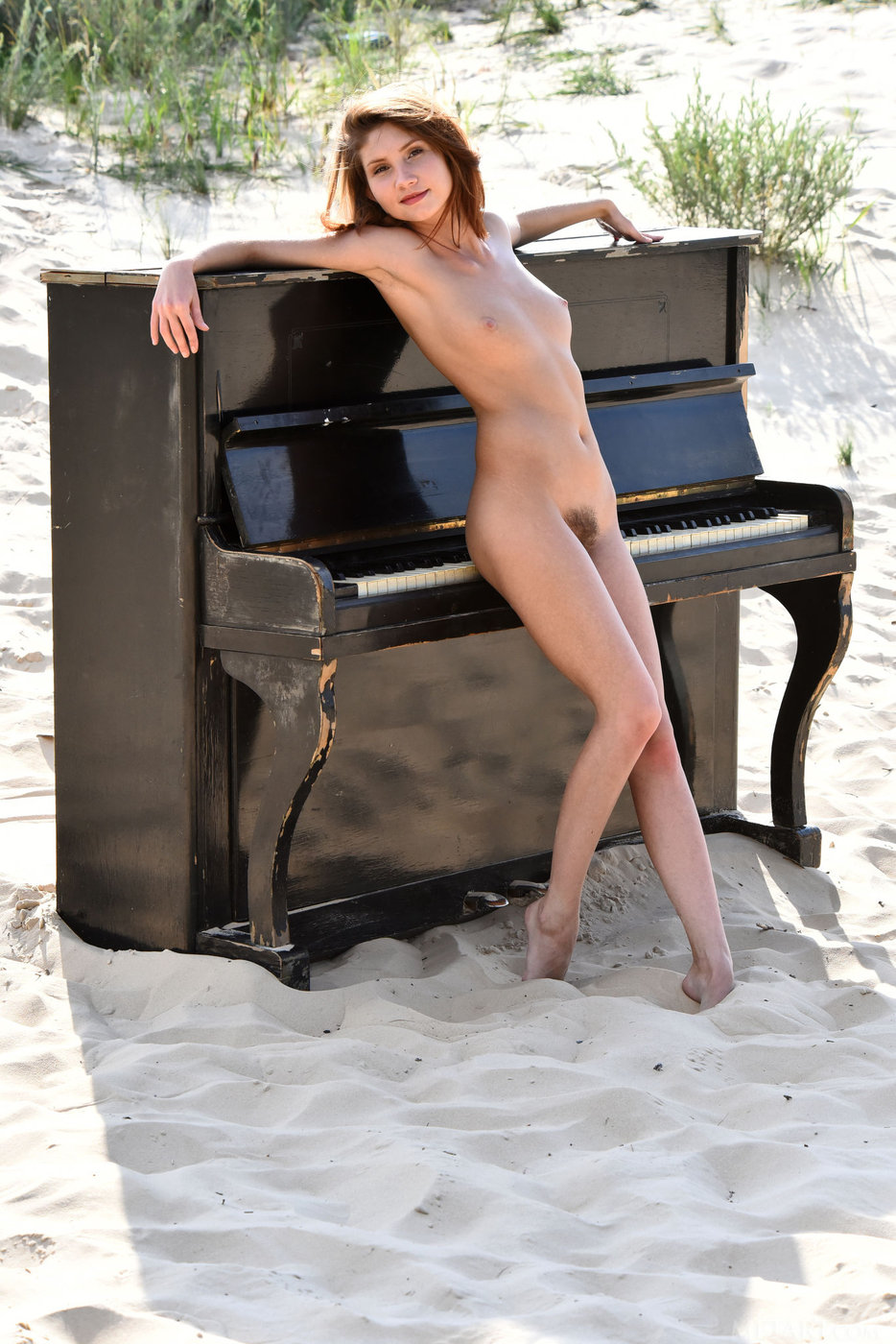 Girl naked on top of a piano with big