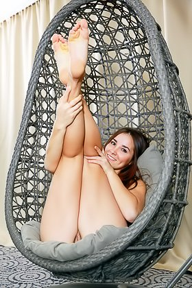 Brunette with tan lines takes off her bra while sitting in an egg chair Videos
