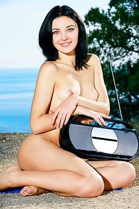 Blue-eyed brunette posing naked next to her boombox-y player Videos
