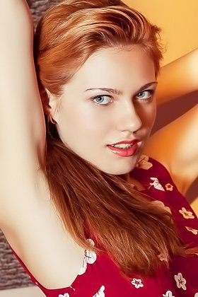 Redheaded cutie dressed in red decides to show her pussy on a couch Videos