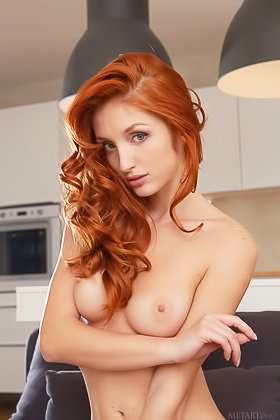Redhead with blue eyes showing off her nude pussy on a grey bed Videos