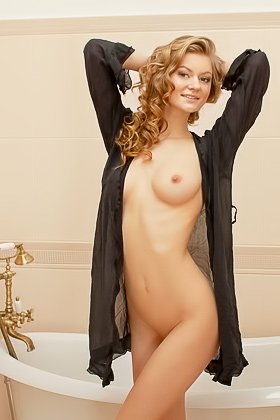 Curly-haired blonde in black seductively posing on top of a bathtub Videos