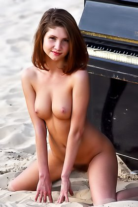 Short-haired chick poses naked, on top of a piano, on a beach Videos