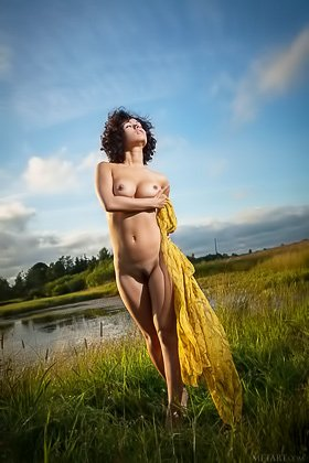 Curly brunette stunner gets completely naked outdoors, by the river Videos