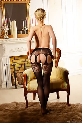 Pale-skinned blonde dressed in black posing seductively on a chair Videos