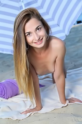 Smiling beauty takes off her black panties to pose naked on a beach Videos