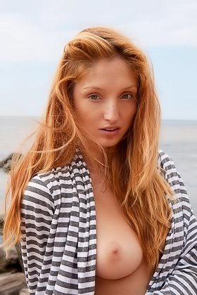 Bronzed redhead takes off her striped outfit on a deserted beach Videos