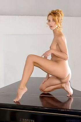 Redheaded girl with a fancy hairdo posing naked on top of a piano Videos