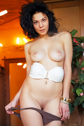Short-haired/curly-haired brunette posing naked in a wicker chair Videos