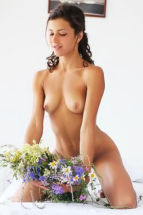 Brunette with unruly hair posing naked next to a bouquet of flowers Videos