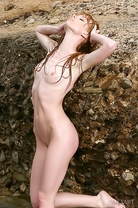 Redheaded chick showing off her all-natural body on a rocky beach Videos