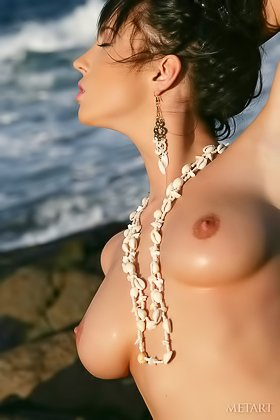 Pouting brunette shows her neatly trimmed pussy on a rocky beach Videos