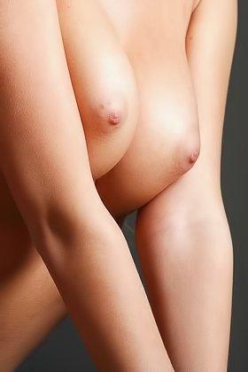 Skinny blonde posing in an armchair with her big boobies exposed Videos